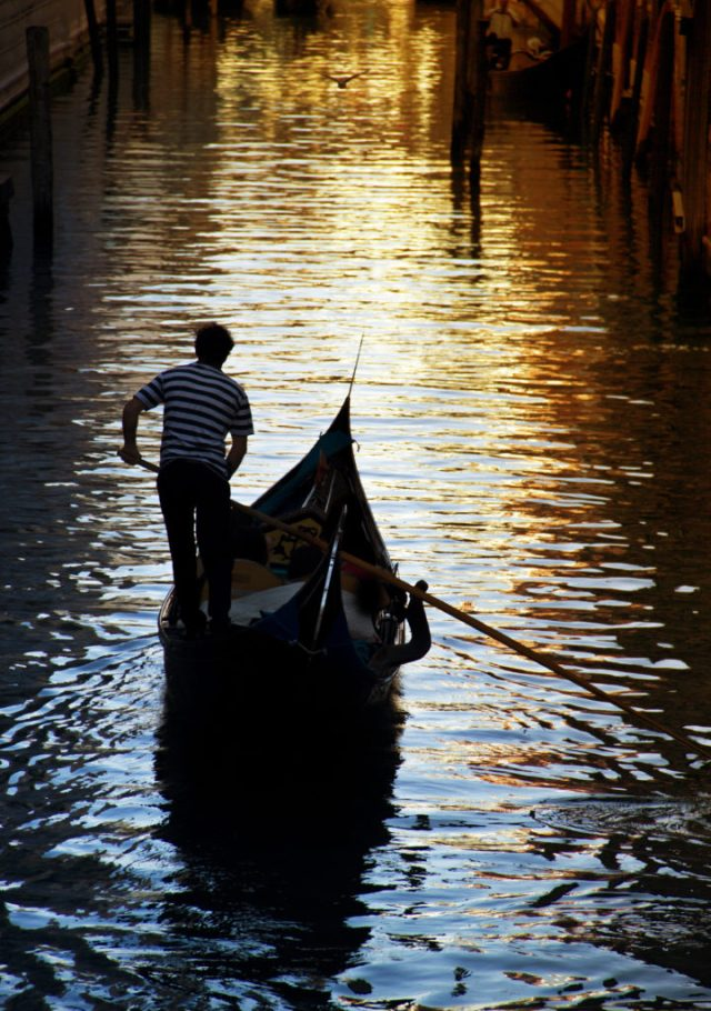Gondolier against beautiful sunset in Venice, Italy